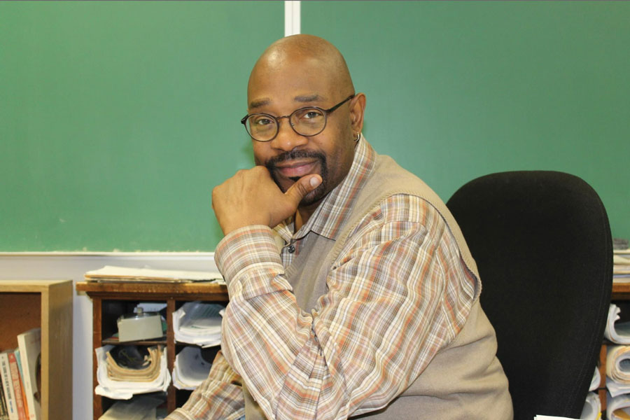 Rodney Lowe sits at his desk. The Journalism Education Association granted Lowe a lifetime achievement award.