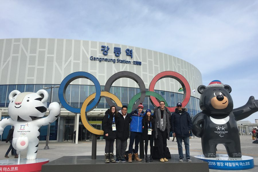 Medill Prof. J.A. Adande and five graduate students pose in front of Olympic rings in South Korea. The group encountered several factors that impacted their reporting during the Winter Olympics, including media access and geopolitical tensions.