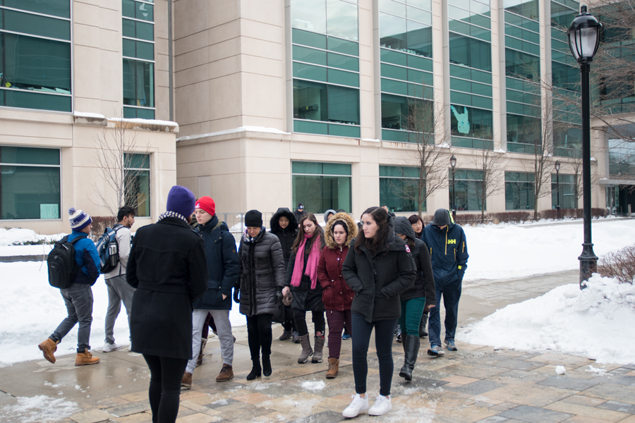 A tour guide directs prospective students across campus. The admissions office is testing new guidelines for its tours that would increase flexibility, highlight inclusivity efforts and cut backward walking.