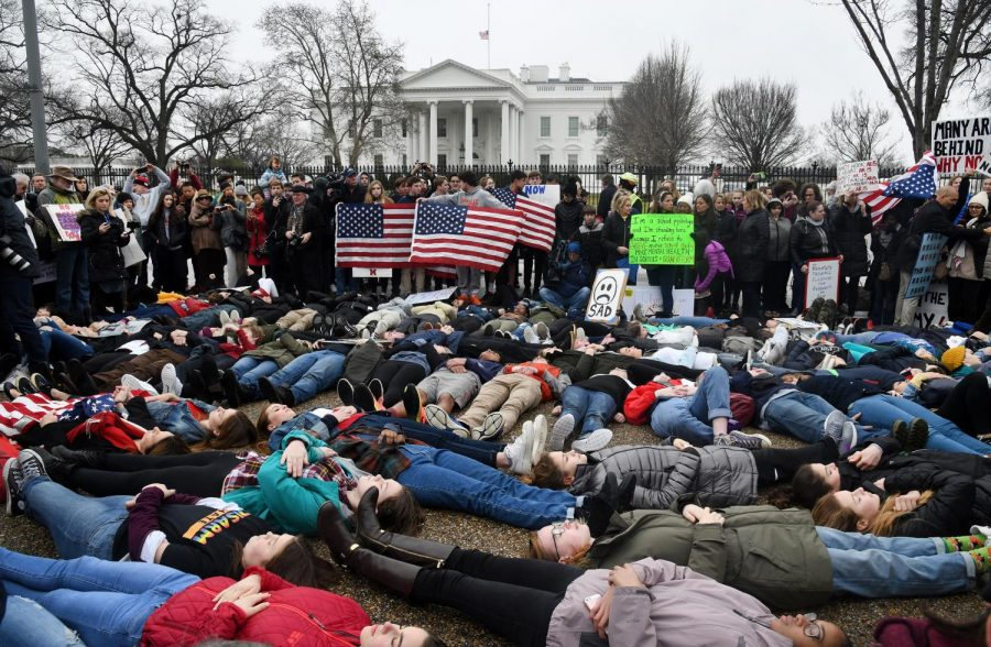 "Students take part in a ""lie-in"" on the road in front of the White House last week after a Florida gunman killed 17 people the week before. Disciplinary action for participation in political demonstrations will not impact admission decisions, the University announced on Friday."