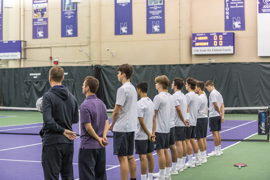 Coach Arvid Swan (left) and interim coach Chris Klingemann (second from left) stand for the national anthem. Swan will be taking a personal leave of absence for health reasons, according to a news release from the athletic department.