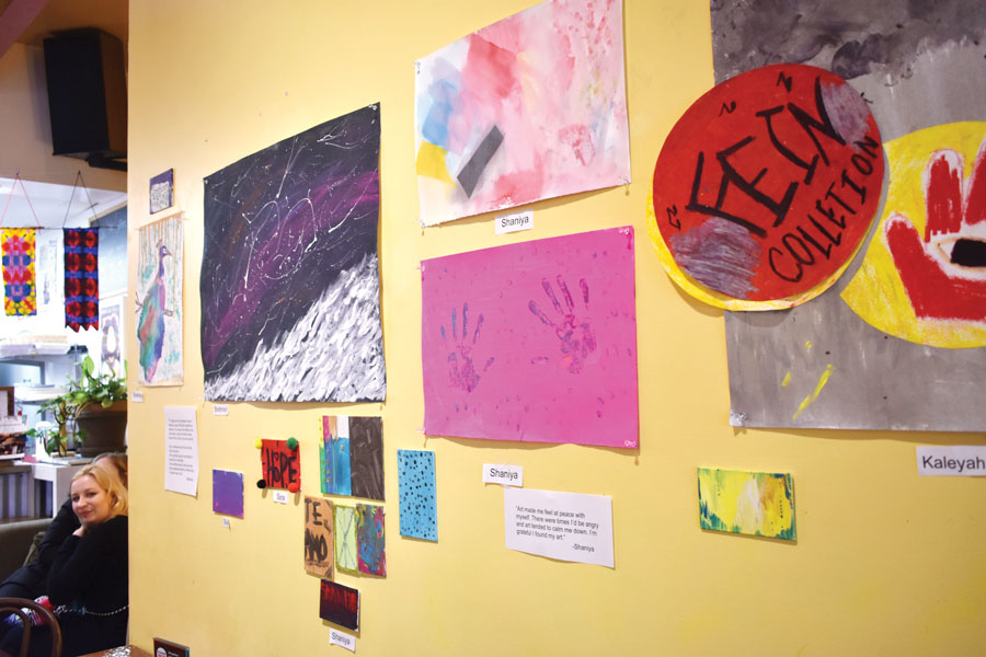 Trainees at Curt's Café South, 1813 Dempster St., showcase their artwork at the exhibition's opening night. Several artists said they were able to express themselves through their art.