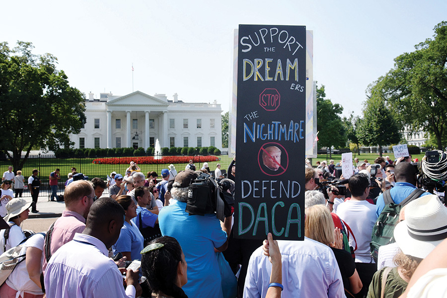 Protesters hold up signs during a rally supporting Deferred Action for Childhood Arrivals, or DACA, outside the White House on September 5, 2017. A federal judge ruled Tuesday that the Trump administration must resume the DACA program and accept new applicants.