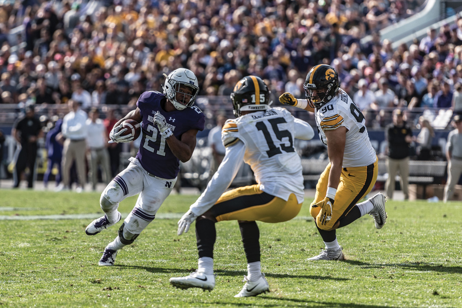 Justin Jackson eyes two Iowa defenders. The longtime Northwestern running back is likely to be chosen by an NFL team during this weekend's draft.