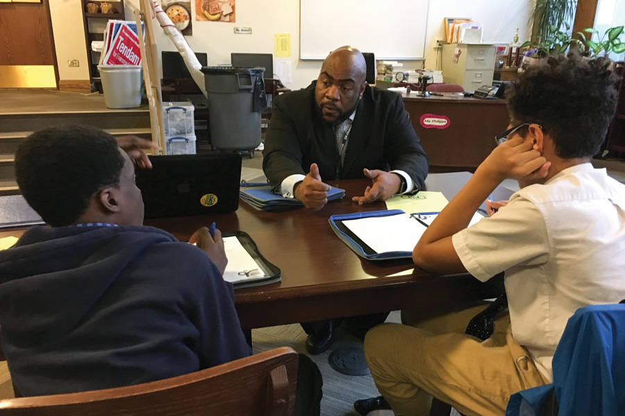 "Nichols Middle School principal Adrian Harries speaks with two students. Following claims that his faculty training practices were discriminatory, the Organization for Positive Action and Leadership and the school board expressed support for Harries, calling the criticisms ""mischaracterizations."""