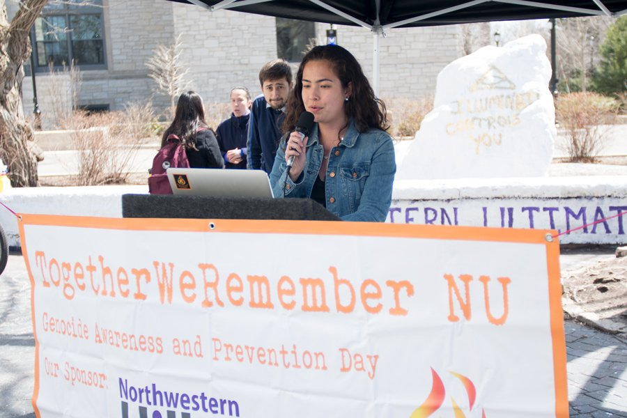 Weinberg sophomore Melana Ellingson reads the name of genocide victims during TogetherWeRemember at The Rock. Ellingson said she volunteered to support the event that promotes awareness of tragedies to prevent them from reoccurring.