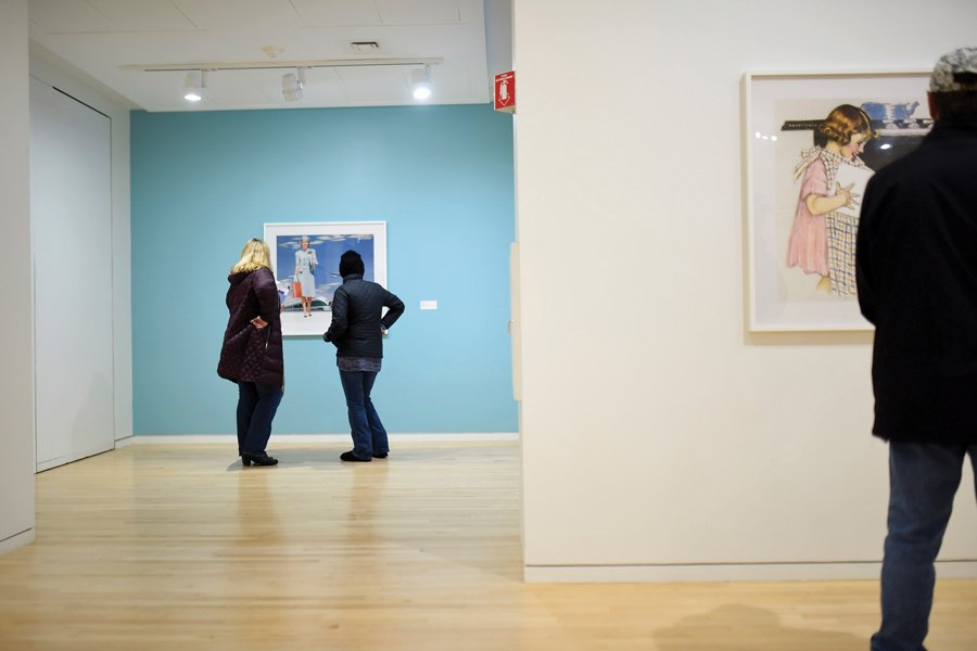 "Gallery visitors look at a piece in ""Hank Willis Thomas: Unbranded"" at The Block Museum of Art. The exhibition opened Saturday and examines the portrayal of African Americans and white women in the media."