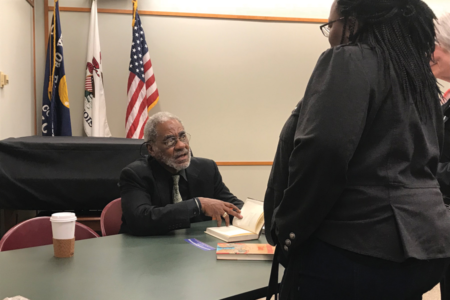 "Charles Johnson signs a copy of his new book, ""Night Hawks,"" at the Evanston Public Library on Tuesday. Johnson, who is a National Book Award winner, was born in Evanston and attended Evanston Township High School."