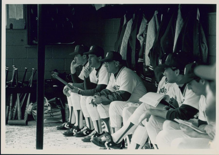 Coach Ron Wellman (far left) and other Northwestern assistant coaches and players look out from the Miller Park dugout. Wellman led the Wildcats to five years of success in the 1980s.