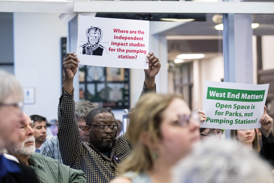 Evanston resident Verzell James holds up sign in protest at City Council meeting Monday. Fifth Ward residents expressed frustration that the city received the award as it planned to install a water pumping station in their neighborhood.