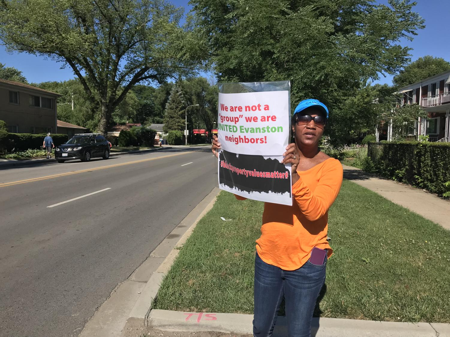 Evanston resident Carolyn Murray stands with a sign protesting a housing project at 2215 Dempster St. Murray was among other Evanston residents protesting the new development early Wednesday morning.