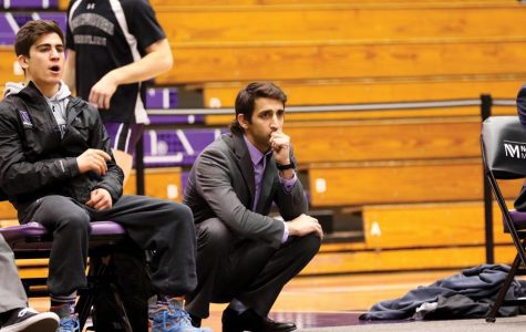 Matt Storniolo squats on the sideline. The wrestling coach has signed a contract extension, NU Athletics announced Thursday.