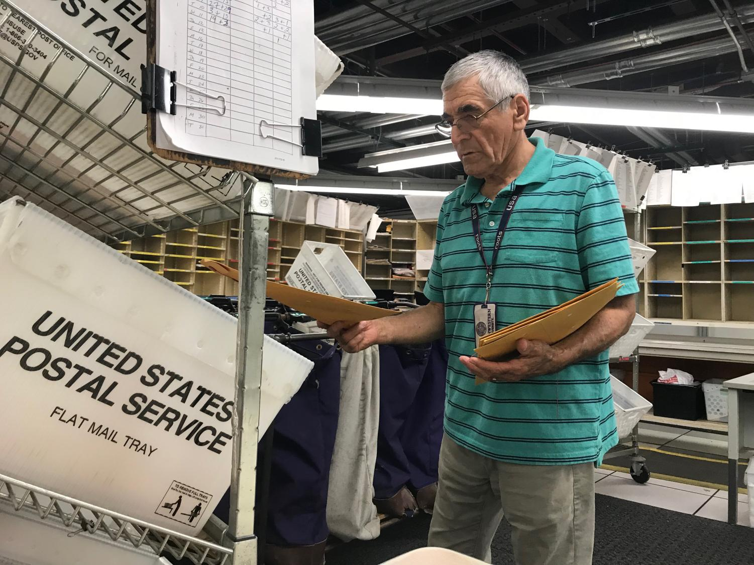 Driver Elvis Acuna sorts a batch of mail in the Northwestern mailroom. Acuna has worked in the  mailroom for over 50 years.