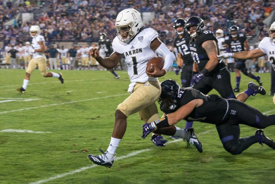 Akron quarterback Kato Nelson scampers away from Northwestern defenders. The loss dropped the Wildcats' nonconference record dating back to 2016 to 3-5.