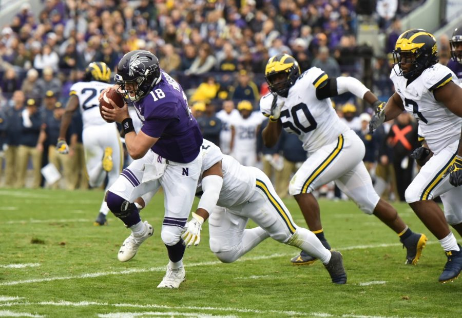 Clayton+Thorson+tries+in+vain+to+escape+a+tackler.+The+Wildcats+blew+a+17-0+lead+in+Saturday%27s+20-17+loss+to+Michigan.