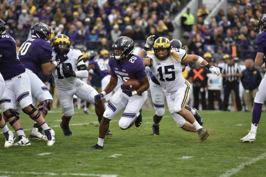 John Moten looks for a hole in the Michigan defense. The junior running back led Northwestern with just 36 rushing yards.