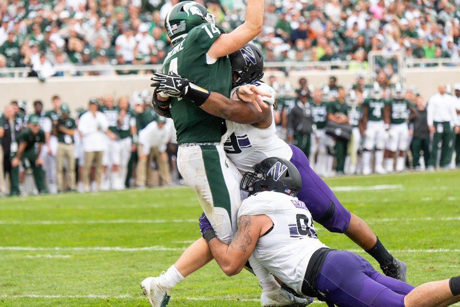 Jordan Thompson and Joe Gaziano converge on Michigan State quarterback Brian Lewerke. The Wildcats' upset win could reverse the course of their season.