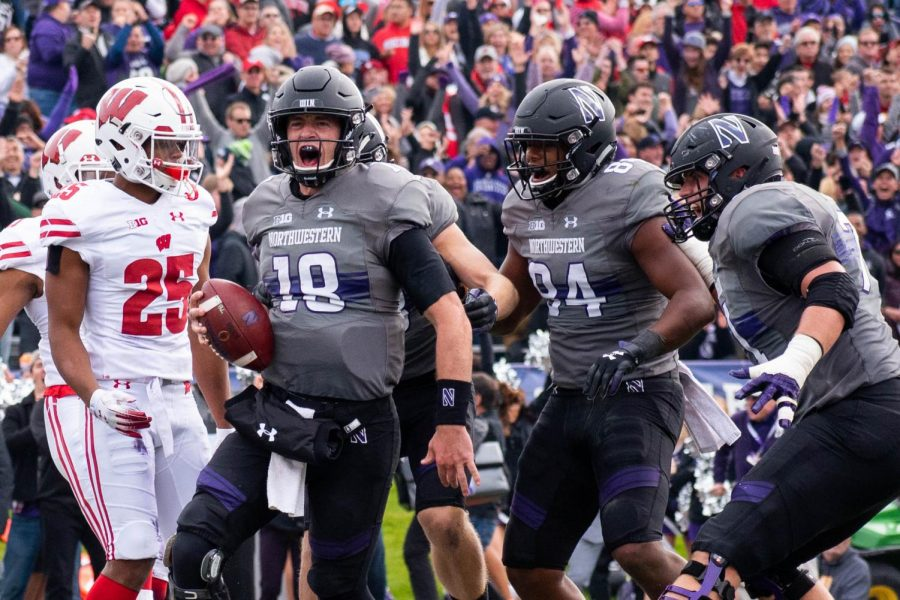 Clayton Thorson celebrates a touchdown. Thorson and the Wildcats secured a landmark win Saturday against Wisconsin.