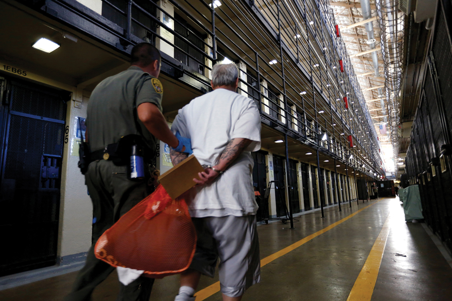 An inmate is escorted back to his East Block cell after spending time in the yard at San Quentin State Prison. Reducing the U.S. prison population now has bipartisan support.