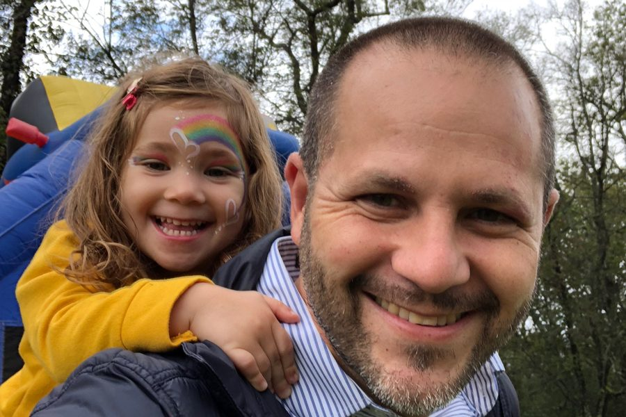 Justin Kanew (Weinberg '01) carries his daughter. Kanew, who is running for Congress, said he hopes to advocate for young people like her through supporting climate change and gun control legislation.