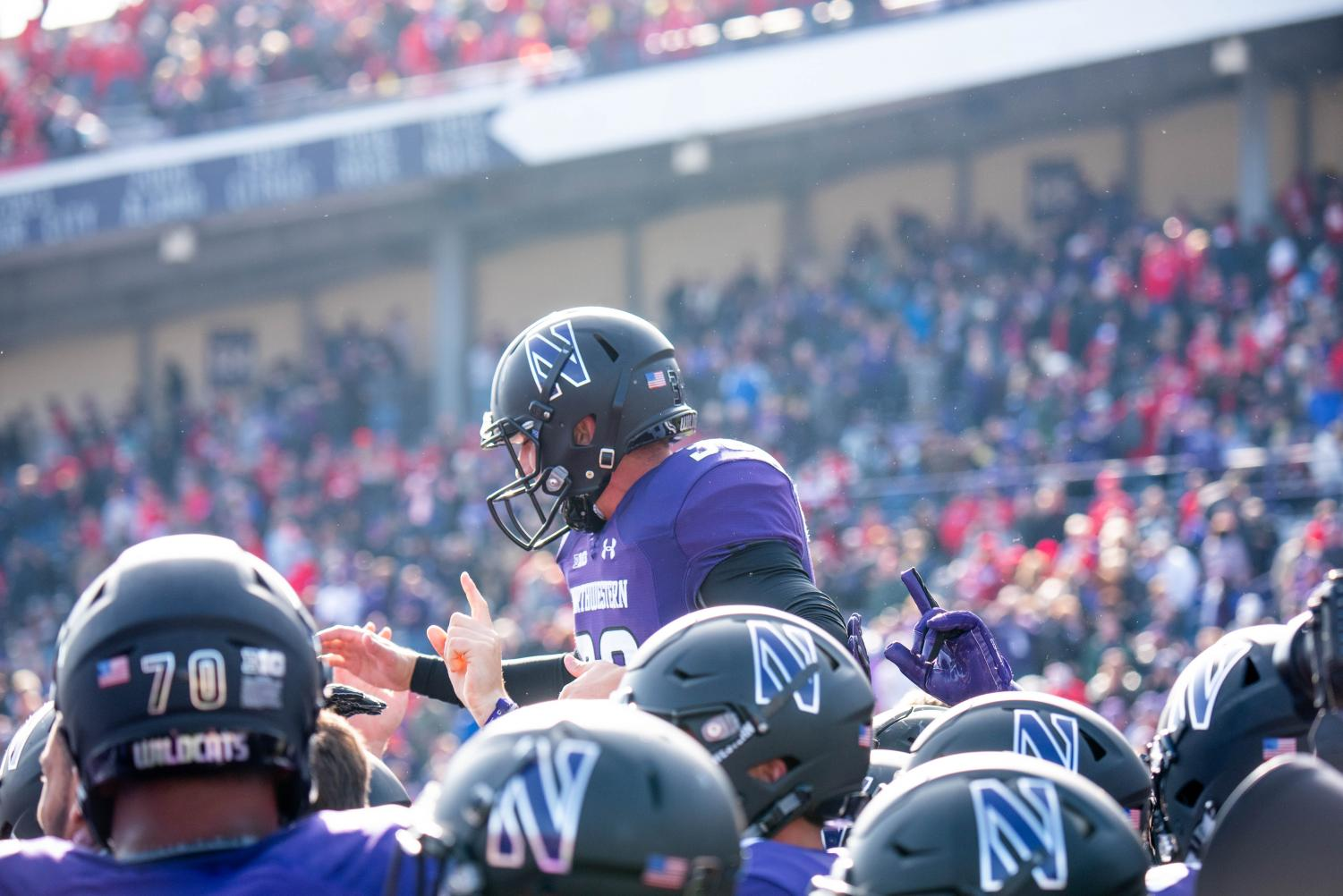 Drew Luckenbaugh is lifted up by his teammates after kicking the game-winning field goal in overtime Saturday. Luckenbaugh made his first two career field goal in Northwestern's win.