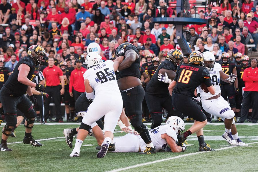 Alex Miller (No. 95) takes on a lineman while Sam Miller (on the ground) reaches for the feet of Maryland quarterback Max Bortenschlager during a game last October. The Miller brothers are both key members of Northwestern's current defensive line.
