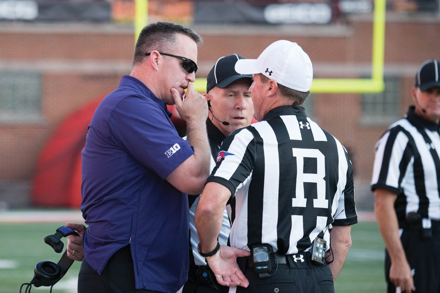 Pat+Fitzgerald+confers+with+officials.+Under+Fitzgerald%2C+the+Wildcats+have+rarely+committed+egregious+penalties.