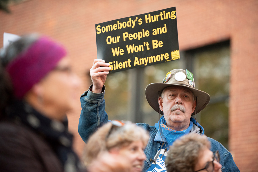 "A man holds a sign outside the Lorraine H. Morton Civic Center. Over 70 residents gathered outside on Monday to protest a number of proposed budget cuts, chanting ""prioritize our people, we shall not be moved."""