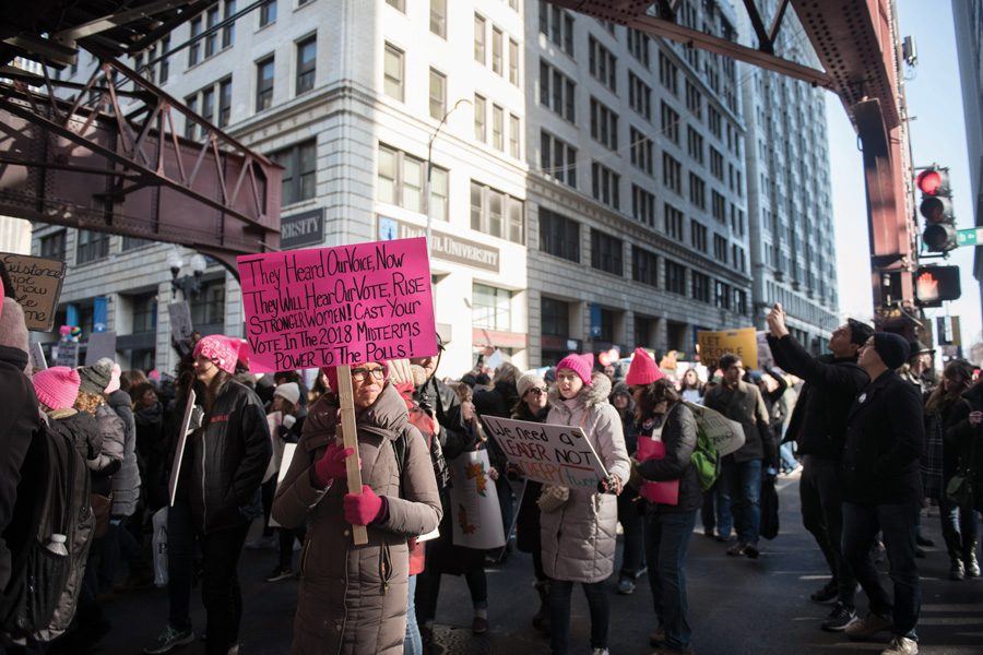 A woman participating in the Chicago Women's March last January calls for supporters of women's rights to vote in the November midterm.