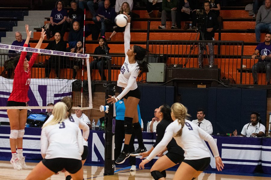 Northwestern volleyball player in white jersey jumps up to slam ball.