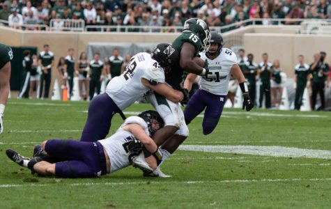 Sophomore linebackers Chris Bergin, a former walk-on, and Paddy Fisher tackle Michigan State running back La'Darius Jefferson earlier this month. Bergin is among several former walk-ons now contributing significantly for Northwestern.
