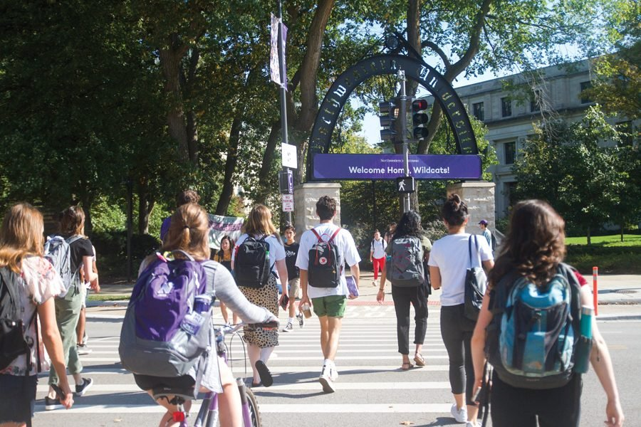 Students crossing Sheridan Road. Recent studies show that school, rather than family, has the biggest role in determining students' political opinions.