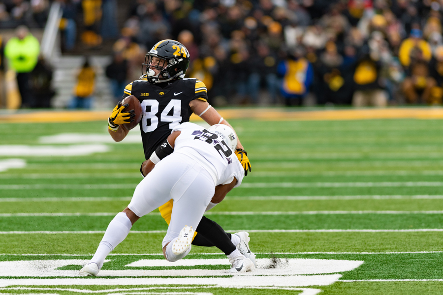 Nate Hall tackles an Iowa player. The Wildcats' win over Iowa help boost NU to No. 22 in the College Football Playoff rankings.