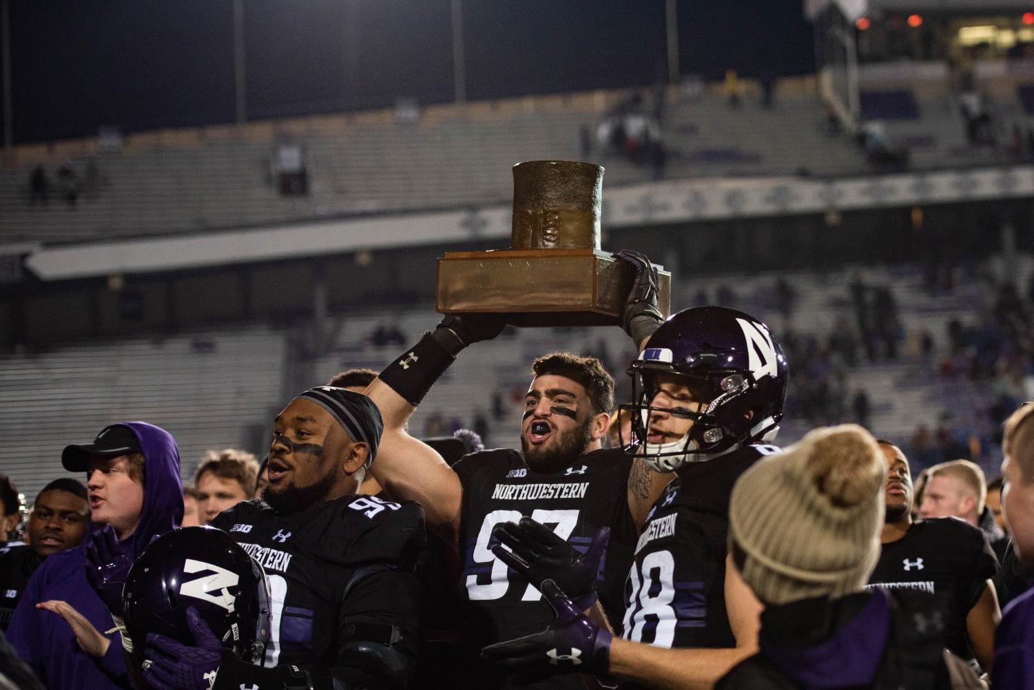 Junior defensive end Joe Gaziano hoists the Land of Lincoln Trophy among his teammates after Northwestern's 24-16 win over rival Illinois at Ryan Field on Saturday.