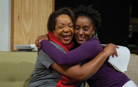 """Two actors embrace while rehearsing for """"Familiar."""" The show, written by actor/playwright Danai Gurira, focuses on a family of Zimbabwean-Americans living in Minnesota."""