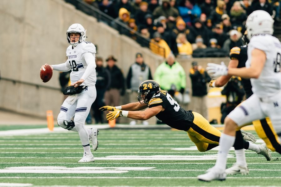 Northwestern+quarterback+Clayton+Thorson+looks+downfield+while+the+Iowa+defense+closes+in.+A+huge+touchdown+pass+to+Ben+Skowronek+lifted+NU+to+a+14-10+victory.
