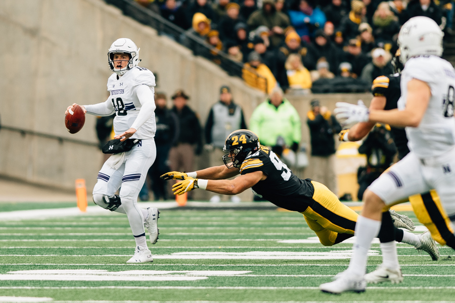 Northwestern quarterback Clayton Thorson looks downfield while the Iowa defense closes in. A huge touchdown pass to Ben Skowronek lifted NU to a 14-10 victory.