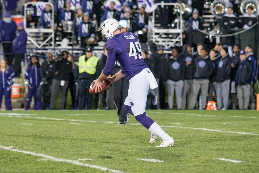 Jake Collins punts the ball into the Evanston night. The senior punter has been one of Northwestern's most consistent performers this season.