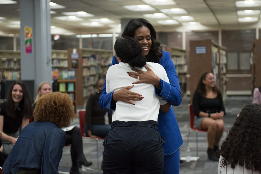 Former first lady Michelle Obama hugs a student at Whitney Young Magnet High School. Obama visited her alma mater Monday in advance of her book tour.