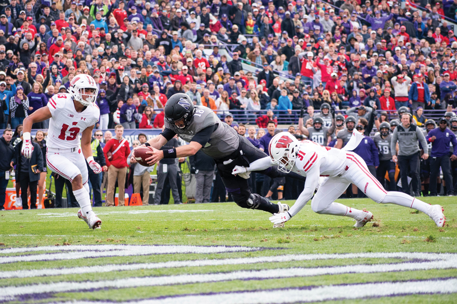 Clayton Thorson dives into the end zone against Wisconsin. The quarterback has seven rushing touchdowns this season despite negative yards.