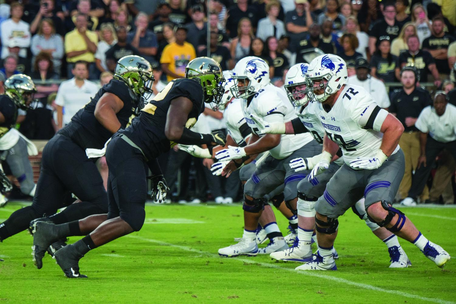 Several offensive linemen prepare to engage blocks. The Wildcats have picked up their play in recent weeks.