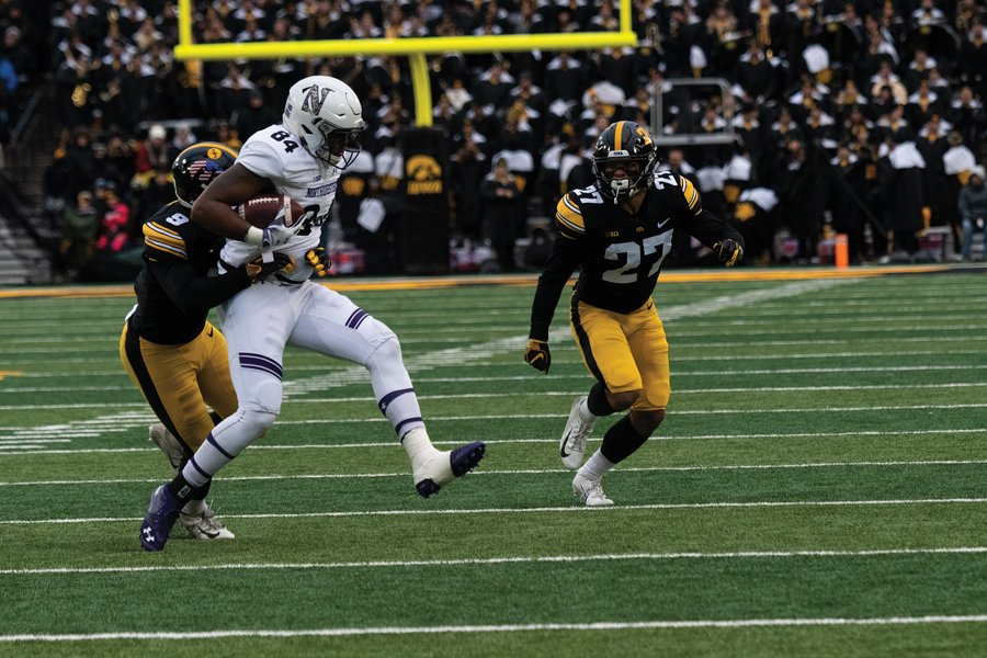 Cam Green fights through a Iowa tackle. The win gave Northwestern a place in Big Ten Championship game, ensuring that they will play 14 games this season.