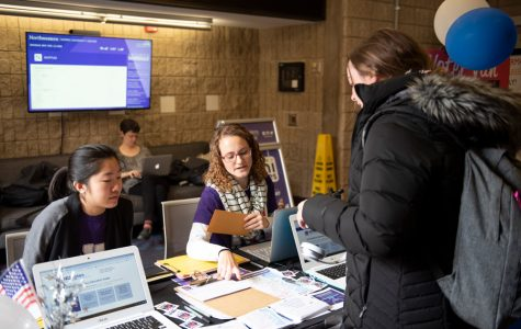 An NU Votes staffer asks a student to fill out a form at the voter van table. NU Votes ramped up its voter turnout initiatives leading up to the midterm elections on Nov. 6.