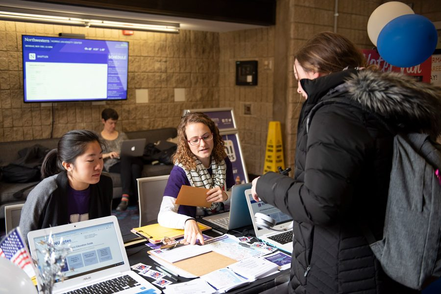 An NU Votes staffer asks a student to fill out a form at the voter van table. According to the group's website, the Center for Civic Engagement and Office of the Registrar both provide ballot notarizations.