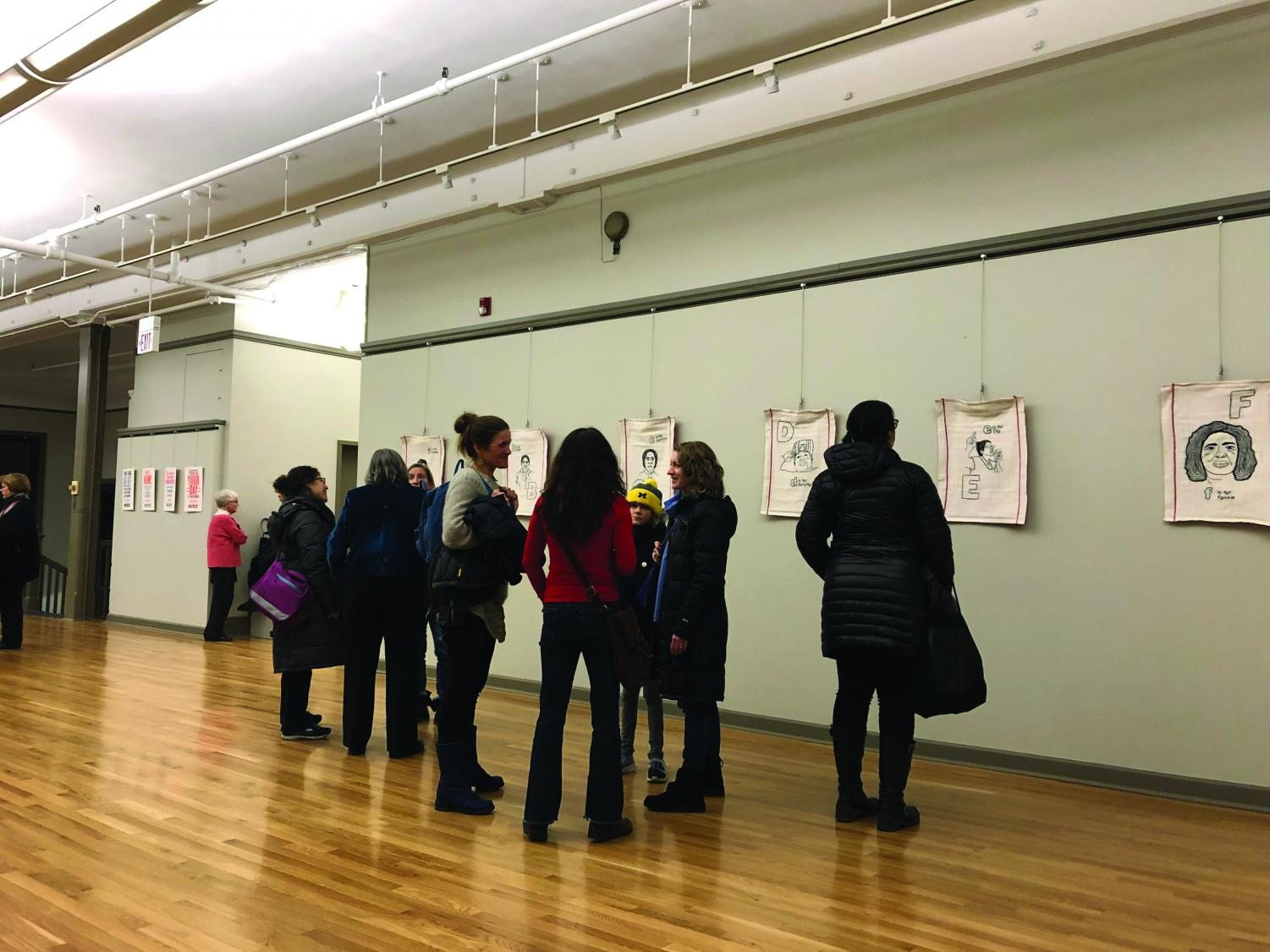"Attendees of the exhibit view Melissa Blount's dishtowel portraits. The exhibit, ""Word,"" debuted at the Noyes Cultural Arts Center on Friday and will run until March 7."