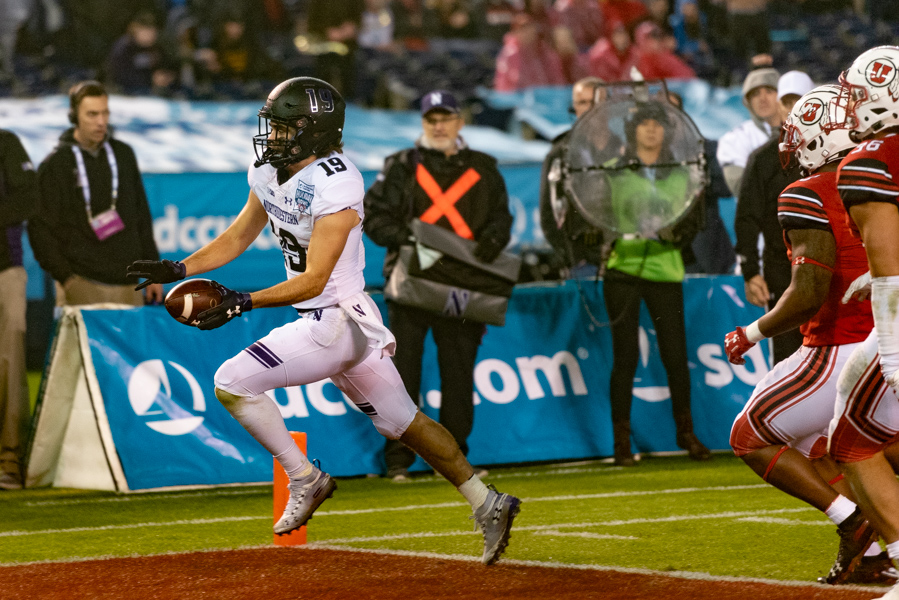 Riley Lees lunges into the end zone for a Northwestern touchdown. His score was one of four in the third quarter that propelled the Wildcats past Utah in the Holiday Bowl.