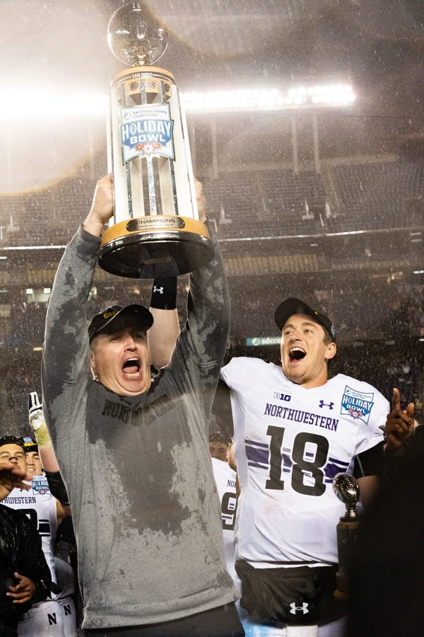 Pat+Fitzgerald+raises+the+Holiday+Bowl+trophy+in+celebration+in+2018.+Fitzgerald+recently+reached+his+100th+win+with+the+Cats.