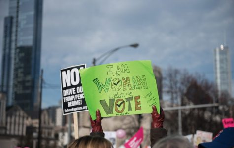 """A sign at the Chicago Women's March 2018 reads """"I am woman, watch me vote."""" Chicago organizers cancelled the event for 2019, citing logistics."""