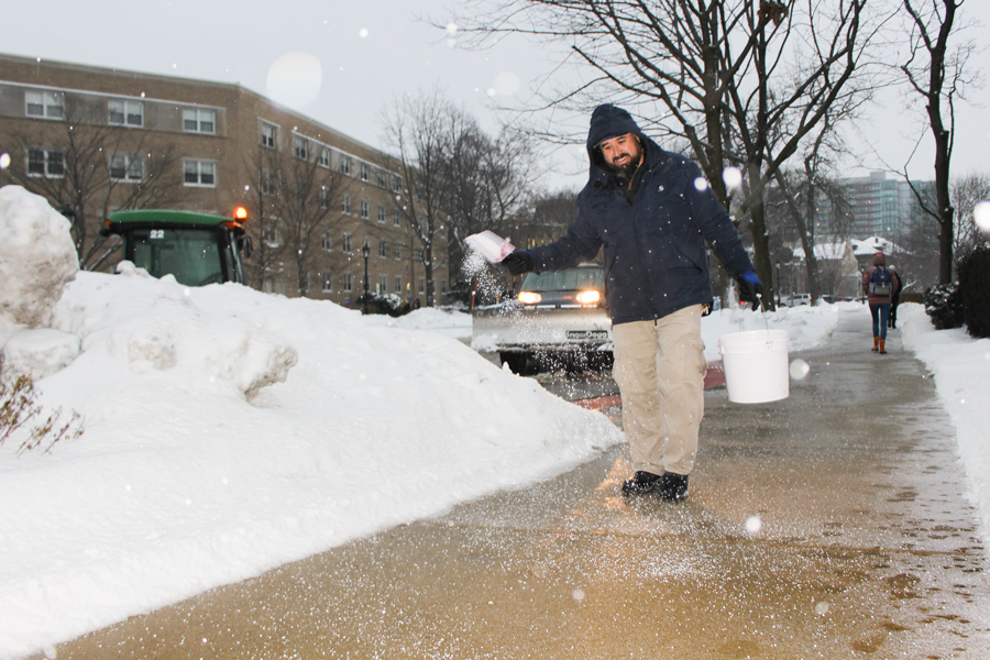 University groundskeeper Marco Montoya spreads salt on south campus. Despite increased clearing efforts, multiple students have reported injuries related to the icy conditions of campus walkways.