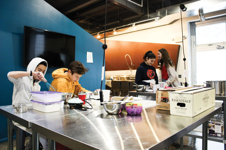 Students practice cooking at Spoonfoolery, a cooking school for kids in Evanston. Spoonfoolery provided meals for federal workers affected by the government shutdown.